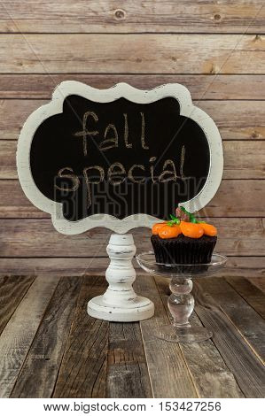 Chalkboard sign and a pumpkin muffin on a glass stand