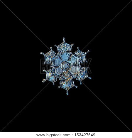Snowflake isolated on black background: macro photo of real snow crystal, captured on glass with LED back light. This is small stellar dendrite snowflake with beautiful short arms and glossy surface.