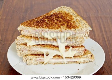 tasty melted cheese and ham sandwiches stacked on a white plate