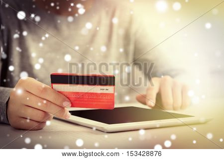Female hands with credit card and tablet, closeup. Snowy effect, online Christmas shopping concept.