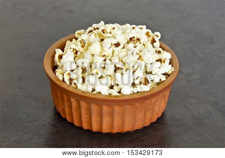 earthenware bowl filled with popcorn on a dark grey background