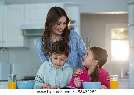Mother with son and daughter having breakfast at home