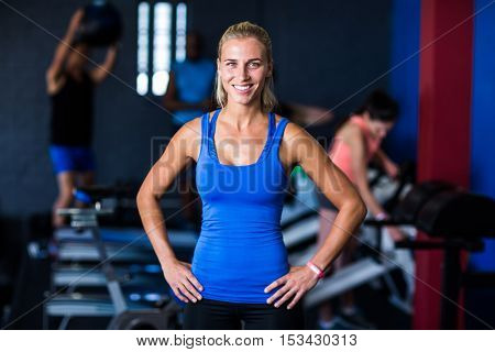 Portrait of happy fit woman with hands on hip while standing in gym