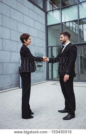 Businesspeople shaking hands in office building