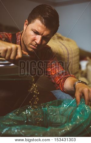 Portrait of adult man pouring raw coffee beans in bag