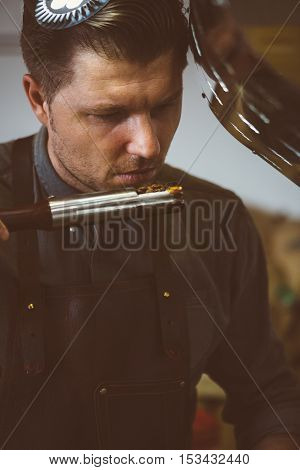 Portrait of professional roaster holding probe of fresh roasted coffee beans and looking at it