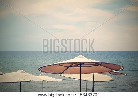 solar umbrellas on the beach and against the background of the sea and the sky