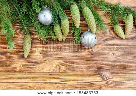 Christmas decorative background. Fur-tree branch with cones and Christmas balls on a wooden background.