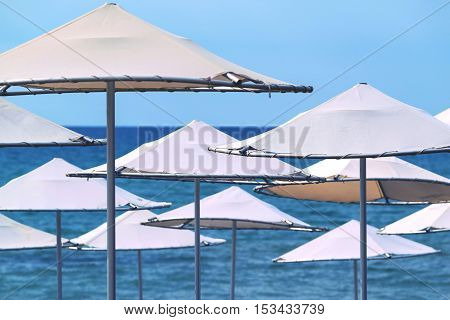 solar umbrellas closeup on the beach and against the background of the sea and the sky
