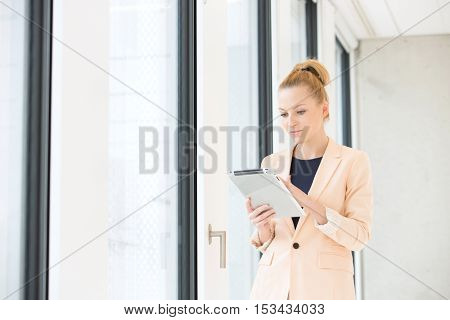 Young businesswoman using tablet computer in office