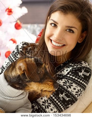 Beautiful young woman smiling, holding dog on lap.