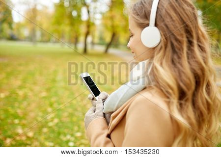season, technology and people concept - close up of beautiful happy young woman with headphones listening to music on smartphone walking in autumn park