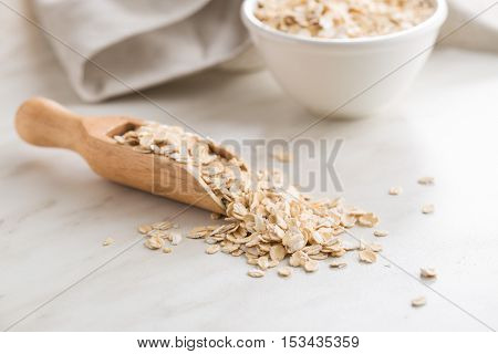 Dry rolled oatmeal in wooden scoop.