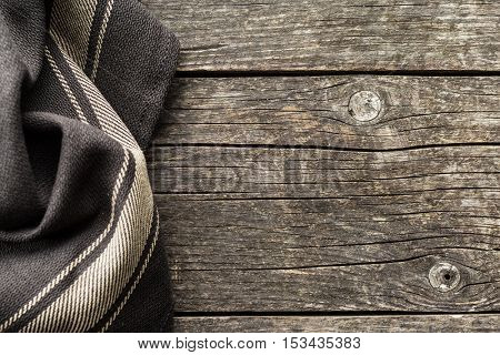 Brown tablecloth over old wooden table.