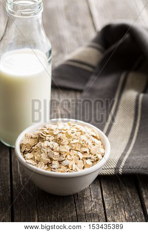 Dry rolled oatmeal in bowl and milk in glass.