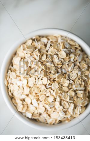 Dry rolled oatmeal in bowl. Top view.