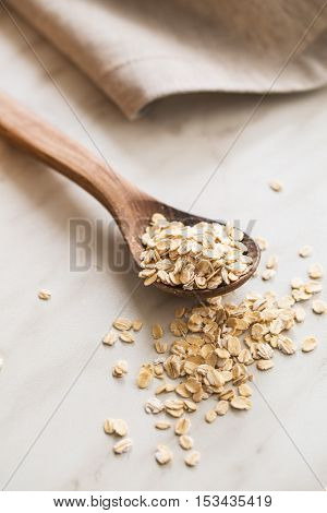 Dry rolled oatmeal in wooden spoon.