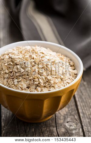 Dry rolled oatmeal in bowl on old wooden table.