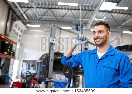 car service, repair, maintenance and people concept - smiling auto mechanic man or smith with wrench at workshop