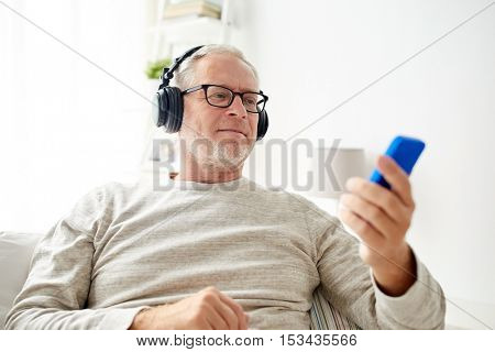 technology, people, lifestyle and leisure concept - happy senior man with smartphone and headphones listening to music at home