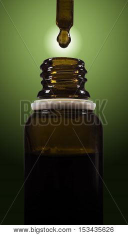 Cannabis oil being droped into a bottle.