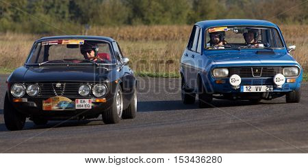 NOGARO, FRANCE - OCTOBER 9: Two old cars, side by side , on a circuit during the Classic Festival, on october 9, 2016, in Nogaro, France.