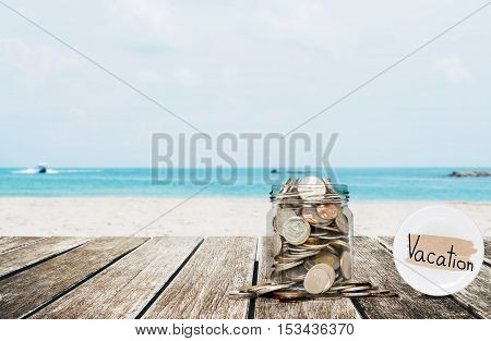 Saving money for vacation concept, glass coins container on wooden table at tropical beach