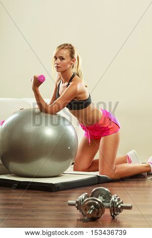 Healthy active lifestyle. Fitness woman with gym ball and dumbbell doing exercise