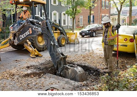 DAYTON,OHIO, USA-OCTOBER 25, 2016:Miller Pipeline workers dig up residential street in St. Anne's Hill Historic District to install new plastic gaslines & outside meters for Vectren Energy Delivery.