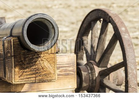 Man made wooden cannon replica in front.