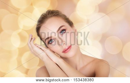 beauty, people and bodycare concept - beautiful young woman face and hands over holidays lights background