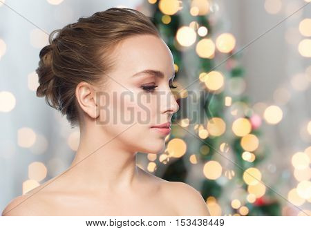 health, people, holidays and beauty concept - beautiful young woman face over christmas tree lights background