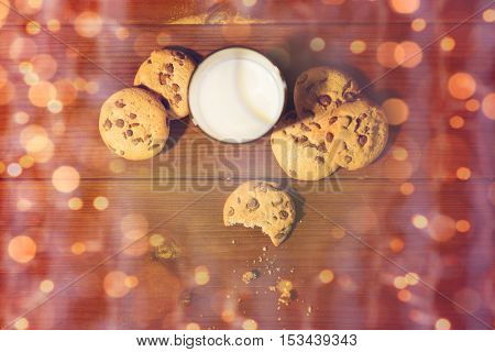 baking, eating, christmas, holidays and food concept - oat cookies and glass of milk on wooden table over lights