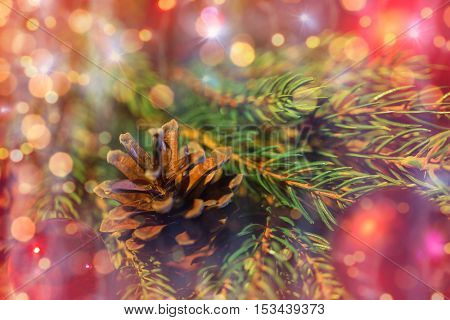 christmas decoration, holidays, new year and decor concept - close up of natural fir branch, ball and pinecone over lights