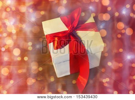 christmas, holidays, presents, new year and celebration concept - close up of gift box with red bow on wooden floor from top over lights