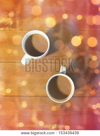 christmas, holidays, winter and hot drinks concept - close up of cups with hot chocolate or cocoa drinks on wooden table over lights