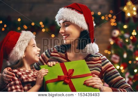 Merry Christmas and Happy Holidays! Cheerful mom and her cute daughter girl exchanging gifts. Parent and little child having fun near Christmas tree indoors. Loving family with presents in room.
