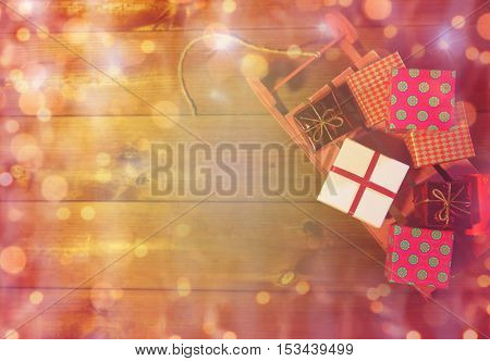 holidays, christmas, advertisement, new year and celebration concept - close up of many little gift boxes on red wooden sleigh over lights