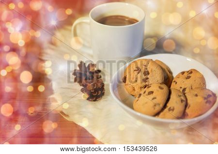 holidays, christmas, winter, food and drinks concept - close up of cups with hot chocolate or cocoa drinks and oat cookies on white fur rug over lights