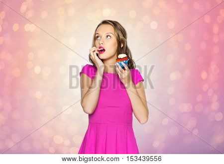 people, holidays, party, junk food and celebration concept - happy young woman or teen girl in pink dress eating birthday cupcake over rose quartz and serenity lights background