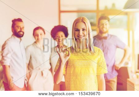 business, startup, people, gesture and teamwork concept - happy young woman showing ok hand sig over creative team in office
