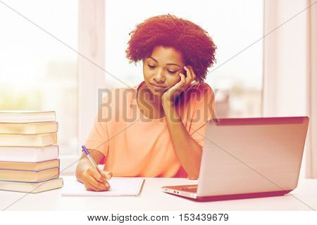 people, technology and education concept - bored african american young woman sitting at table with laptop computer and books and writing to notepad at home