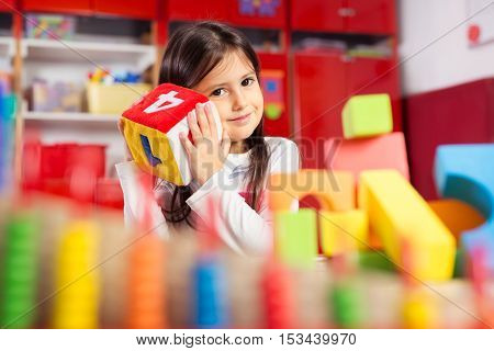 Preschooler child playing with colorful toy blocks.