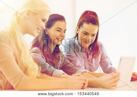 technology, internet, school and education concept - group of smiling teenage students with tablet pc computer at school