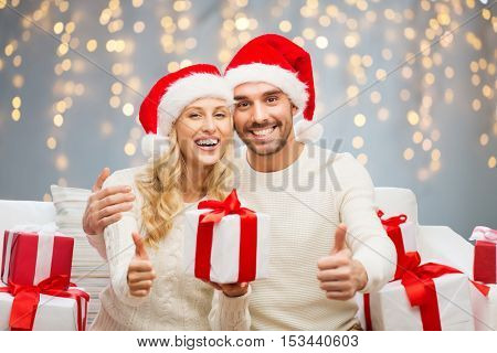 christmas, holidays and people concept - happy couple in santa hats with gift boxes sitting on sofa and showing thumbs up over lights background