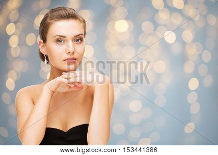 beauty, jewelry, holidays and people concept - beautiful woman in evening dress wearing diamond earrings over lights background