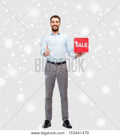 people, shopping, christmas, winter and holidays concept - smiling man holding red sale sign and showing thumbs up gesture