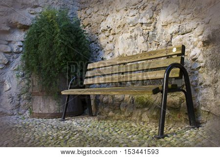 wooden bench near a old stone wall