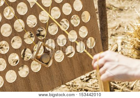 Old wooden ball game design played hand with two strings.