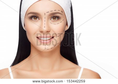 Young woman with perforation lines on her face before plastic surgery operation. Beautician touch and draw correction lines on woman face. Isolated